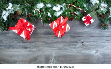 Snow covered Christmas tree evergreen branches with gifts placed on top of a rustic wooden background
