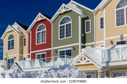 Snow covered colorful condominiums.
