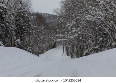 A snow covered country road in rural Vermont after a winter storm. The trees are covered in snow after the snowstorm. The road has not been plowed, it is covered in white snow in the winter.