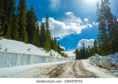 Snow Covered Dirt Road by a Snowbank in the Mountains