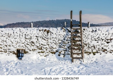 Snow covered dry stone wall in the Derbyshire Peak District,  Ladder style against a cold blue sky.