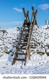 Snow covered dry stone wall in the Derbyshire Peak District,  Ladder stile against a cold blue sky.