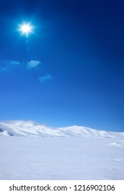 Snow covered empty frozen landscape of mountainside over blue sky with sunbeam