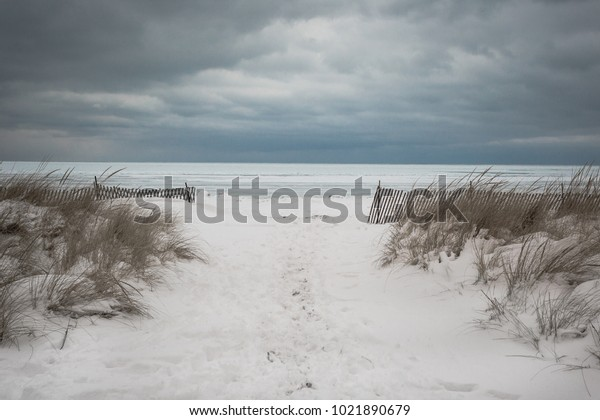 Snow covered entry to beach with wild grass and gloomy clouds