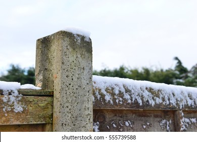 A snow covered fence in winter in the UK.