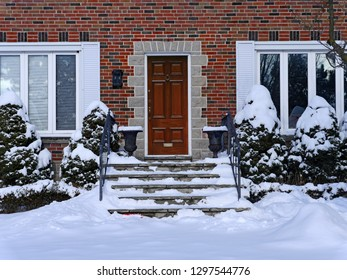 snow covered front steps of brick house with elegant wooden door