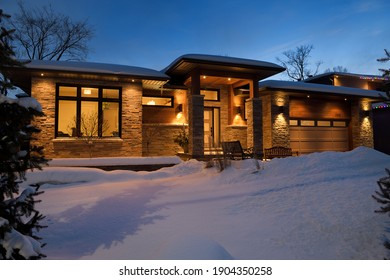 Snow covered front yard of modern house in Ontario Canada at twilight