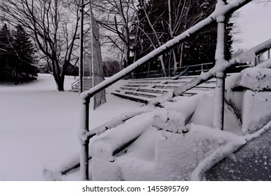 Snow covered handrail with blurred seating covered with snow in the background.