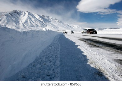 Snow covered highway in winter with the cars passing by and mountains in the distance