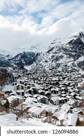 With snow covered houses in Zermatt village, Valais, Switzerland.
