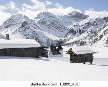 Snow covered huts with mountains in background, Davos, Grisons, Switzerland