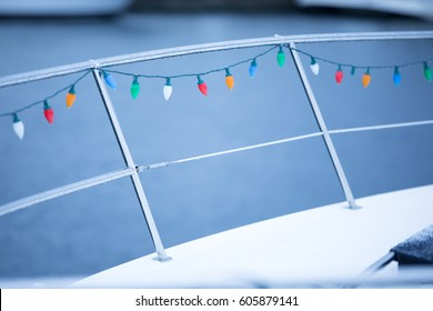 Snow covered motor boat deck with Christmas light strand on chrome railing