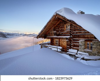 Snow covered mountain hut old farmhouse in the ski region of Saalbach Hinterglemm in the Austrian alps at sunrise against blue sky