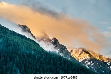 Snow covered mountain peaks and colorful clouds over mountain range during sunset, Arkhyz villadge, Caucasus mountains, Russia