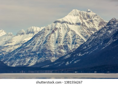 snow covered mountain peaks in winter above a frozen, icy lake, Glacier National Park, Montana