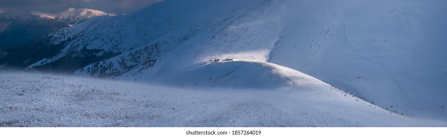 Snow covered mountain slope in last evening sunlight. Magnificent windy dusk on picturesque alpine ski resort, Dragobrat, Ukraine, Carpathian Mountains.
