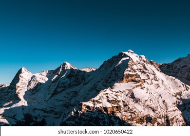 Snow covered mountain in the Swiss Alps on a sunny day with blue sky, Switzerland