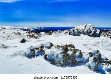 SNow covered mountain tops of Back Perisher mountain peak with rocks and moss on a cold sunny winter day during skiing season.