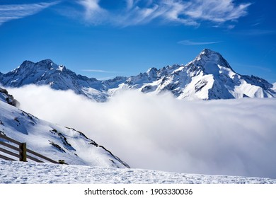 Snow covered mountains above clouds