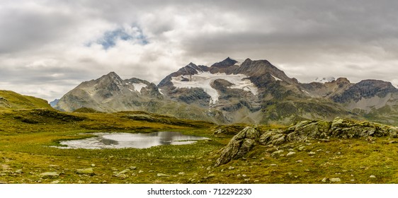 Snow covered mountains below dramatic sky and small alpine lake in front