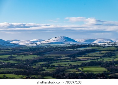Snow covered mountains of Caer Caradoc and the Long Mynd that overlook Church Stretton from Wenlock Edge region, UK