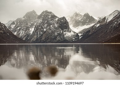 Snow covered mountains with lake foreground and its reflection in sepia mood.
