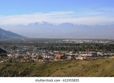 Snow covered mountains towering above the suburbs near Palm Springs, CA