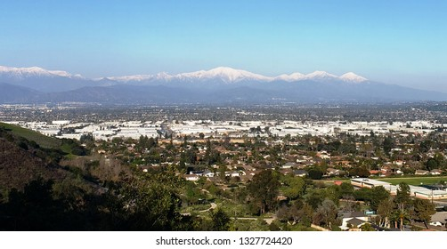 Snow covered mountains towering over suburbs, California