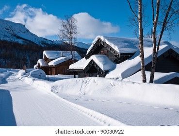 Snow covered norwegian mountain cottages at a sunny day at easter