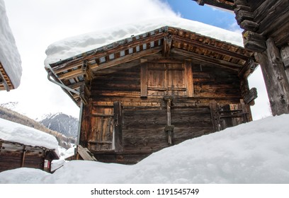 Snow covered old houses made of wood in alpine valley in Switzer