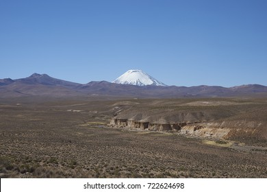 Snow covered Parinacota volcano (6342m) towering above the Altiplano and cliffs running along the valley of the River Lauca in Lauca National Park, northern Chile.