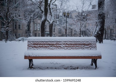 Snow covered park bench with first snow