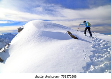 Snow covered peak and a woman skier ascending in windy conditions, Les Deux Alpes, France