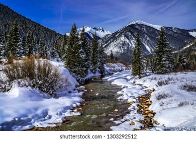 Snow covered peaks in the distance covered with freshly fallen snow in mountain valley with river flowing through alpine forest with trees and rocks