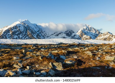 Snow covered peaks and ground covered with grass and stones. Amazing nature of north land of Norway.