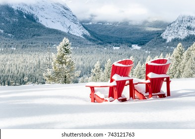 Snow Covered Red Adirondack Chairs Facing a Frozen Forested Valley on a Winter Day. Banff National Park, AB, Canada.