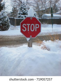 Snow covered red stop sign in snow drift on residential street..