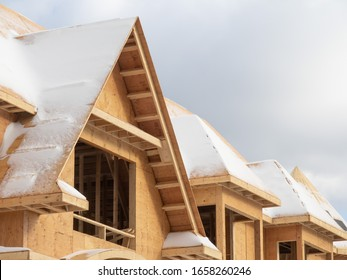 a snow covered residential construction project roof in winter