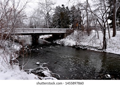 A snow covered road bridge over the open water of the Pike River in a Wisconsin park early in the winter season.
