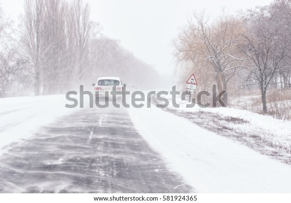 Snow covered road, winter driving with sign - slippery