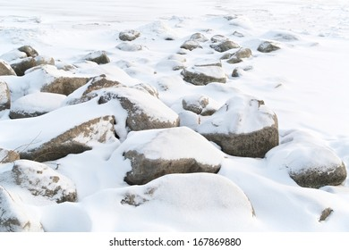 Snow covered rocks at the edge of the lake