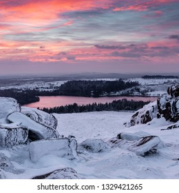 Snow covered rocks on Sheeps Tor in the Dartmoor National Park at sunset with Burrator reservoir in the distance.