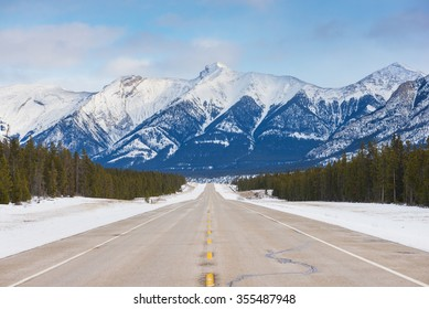 Snow covered Rocky Mountains and highway in Alberta, Canada.