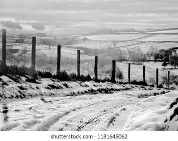 A snow covered rural landscape with a narrow single lane country road with tyre tracks running down a steep hill with a fence alongside with fields and farms on surrounding hills with in yorkshire