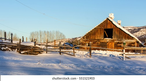 Snow covered rustic cabins in the woods in winter.