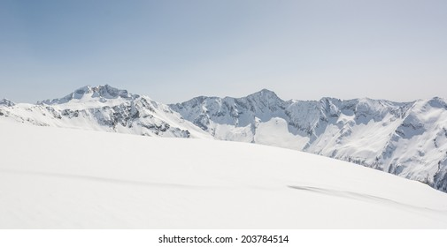 Snow covered slope in front of mountain ridge, view from Ankogel, Austria