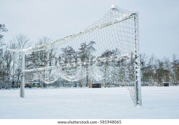 Snow covered soccer field with goal during winter
