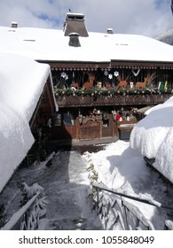 Snow covered stairs lead down to a restaurant in small alpine village of Chatel, France