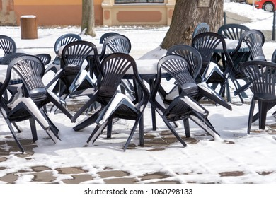 snow covered tables and chairs in a beer garden