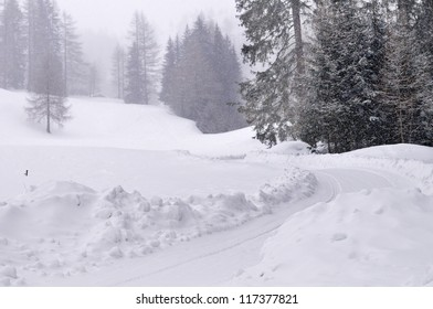 Snow covered track under snowfall in mountain landscape with forest in high Val Casies (Gsiesertal) in Alto Adige, Italy